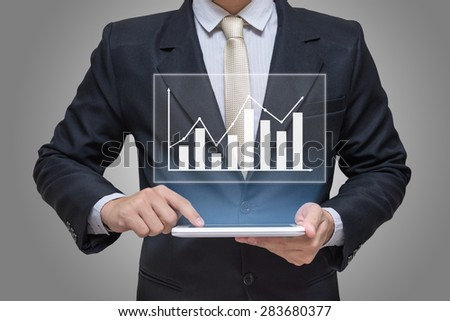Businessman hand holding tablet graph finance on gray background - stock photo