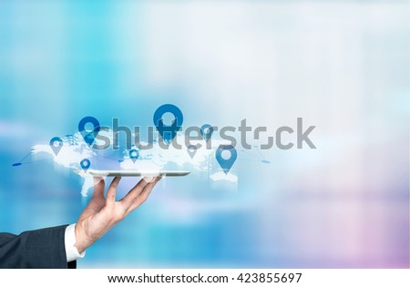 Businessman hand holding tablet with abstract map and location pins. Traveling concept - stock photo