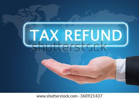 Businessman hand holding tax refund on virtual screen - stock photo