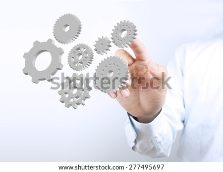 Businessman hand is pointing the gears on the transparent virtual screen. - stock photo