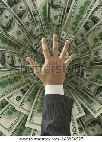 Businessman hand over money hole - stock photo