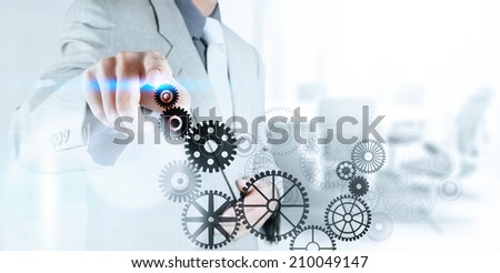 businessman hand pushing gear to success concept on touch screen computer - stock photo