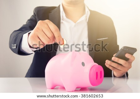Businessman Hand Put Coins To Piggy bank - stock photo
