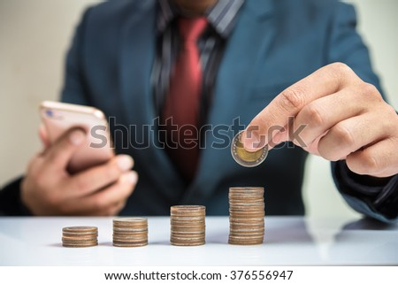 Businessman Hand Put Coins To Stack Of Coins  - stock photo