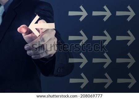 Businessman hand selecting different arrows as leadership concept - stock photo