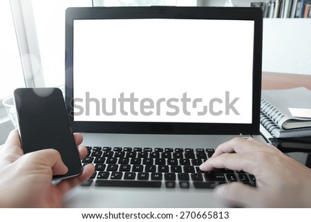 Businessman hand using blank screen laptop and mobile phone in office - stock photo
