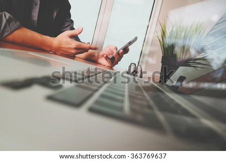 Businessman hand using mobile phone with laptop computer as business strategy concept - stock photo