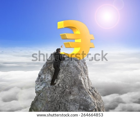 Businessman hand wanting for gold euro symbol on mountain peak with sunlight cloudscape background - stock photo