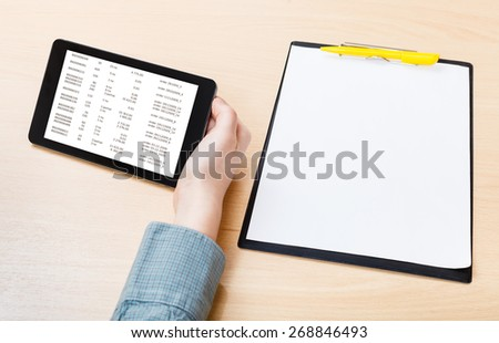 businessman hand with tablet PC with data on screen at office table - stock photo