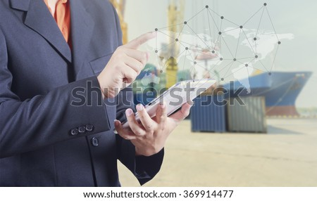 Businessman hand working and smart phone and laptop on Industrial Container Cargo freight ship background (Elements of this image furnished by NASA)  - stock photo