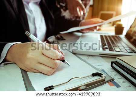 businessman hand working with new modern computer and writing on the notepad strategy diagram as concept morning light - stock photo