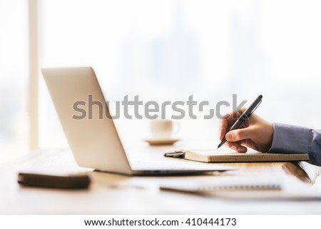 Businessman hand writing in notepad on office desk with laptop and various blurry items - stock photo