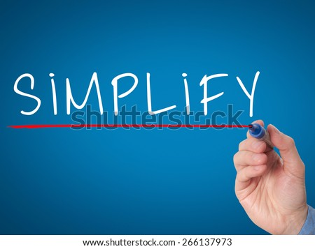 Businessman hand writing Simplify with marker on transparent wipe board isolated on blue. Stock Image - stock photo