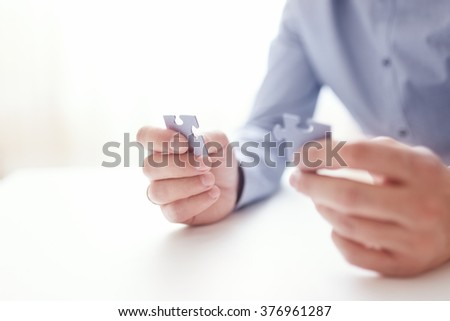 Businessman hands connecting jigsaw puzzle. Business solutions, success and strategy, learning concept. Close up photo with small dof - stock photo