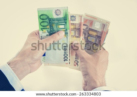 Businessman hands counting money, Euro currency (EUR), in vintage tone - stock photo