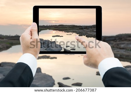 Businessman hands holding tablet taking pictures Sam Phan Bok rock canyon beside Khong river - stock photo