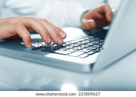 businessman hands pushing keys of laptop - stock photo