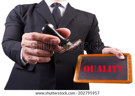 businessman hands put the stamp wood blackboard red quality word stamp on white background with clipping path - stock photo