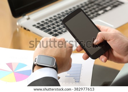 Businessman hands synchronizing on line a smart watch and phone sitting in a desktop at office with a computer in the background - stock photo