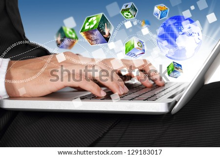 Businessman hands typing on laptop keyboard connection the world with industrial cubes streaming - stock photo