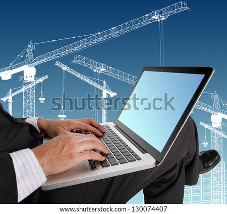 Businessman hands typing on laptop keyboard  with crane illustration background - stock photo