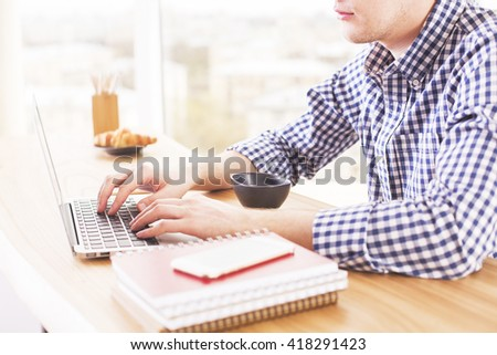 Businessman hands using laptop on wooden desk with coffee, croissant, smartphone and notepads - stock photo