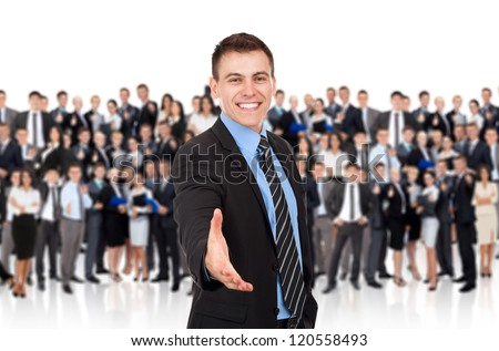 businessman handshake, hold hand welcome gesture, Handsome young excited business man happy smile shake hand over big group of businesspeople crowd background - stock photo