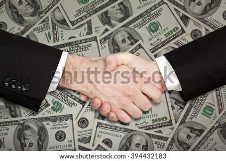 businessman handshake isolated on hundred dollar money - stock photo