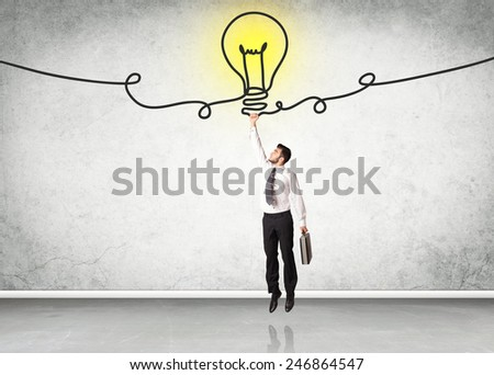 Businessman hanging on an idea bulb  - stock photo