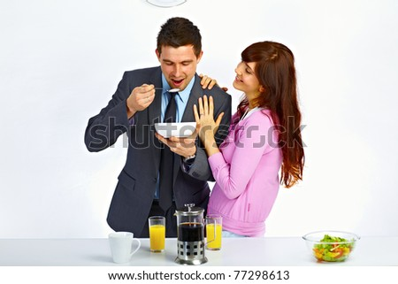 Businessman has breakfast before go to work and his wife standing near him and hugging him - stock photo