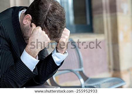 businessman has to much of work and sitting on a bench - stock photo