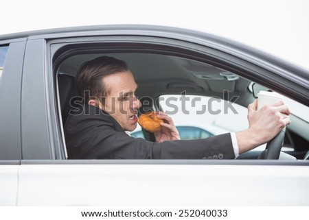 Businessman having coffee and doughnut on the phone in his car - stock photo