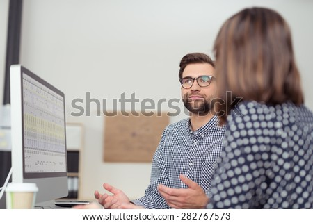 Businessman having discussion with a female colleague as they sit together in front of a computer gesturing with his hands as he explains something, view over her shoulder - stock photo