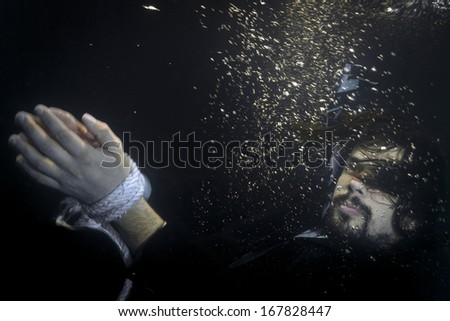 Businessman having his hands tight with rope thrown in the river, sinking,underwater shot. - stock photo