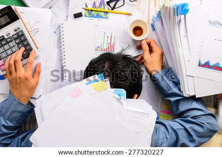 Businessman heavy workload sleep at office desk with finance sheet calculator and coffee.(concept for overworked) - stock photo