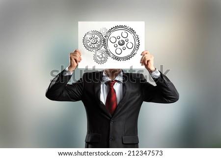 Businessman hiding face behind paper sheet. Working business mechanism - stock photo