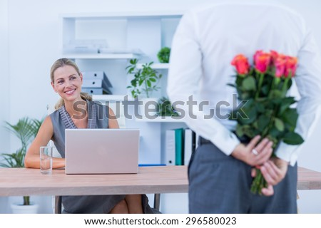 Businessman hiding flowers behind back for colleague in the office - stock photo