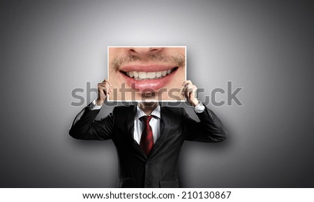 Businessman hiding head behind photo with huge mouth - stock photo