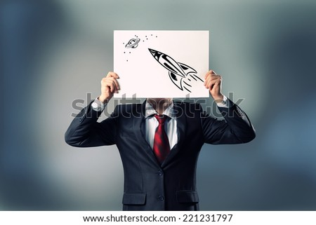 Businessman hiding her face behind paper sheet with sketches - stock photo