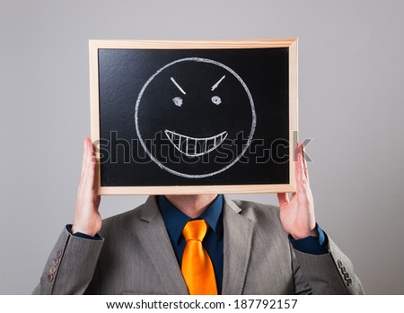 Businessman hiding his face with a white billboard with a evil face on it - stock photo