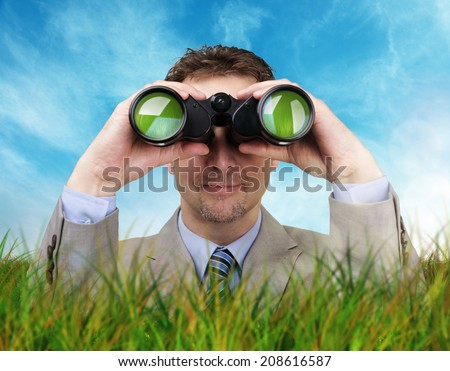 Businessman hiding in the long grass looking through binoculars searching for answers concept for business creativity or environmental conservation - stock photo