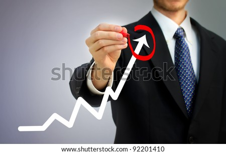 Businessman highlighting business growth on a graph - stock photo