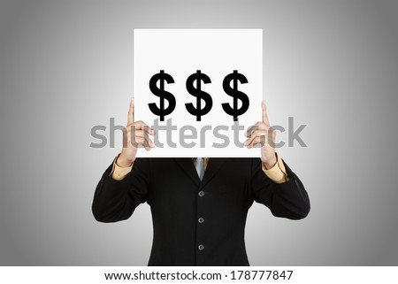 Businessman hold board with money sign on gray background - stock photo