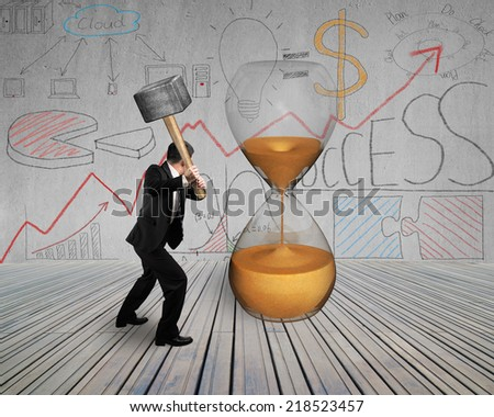 businessman hold hammer to hit sandglass with doodles and wooden floor - stock photo