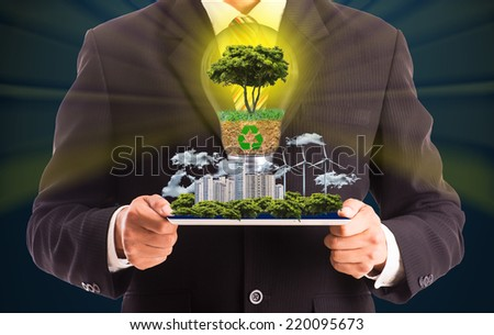 Businessman hold tablet for show green city and engergy for your future world - stock photo