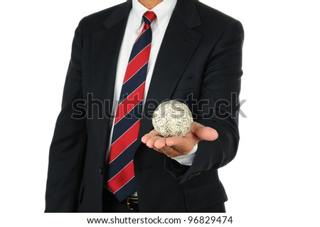 Businessman holding a ball of money in the palm of his hand. Man is unrecognizable, wearing a suit and tie over a white background. - stock photo