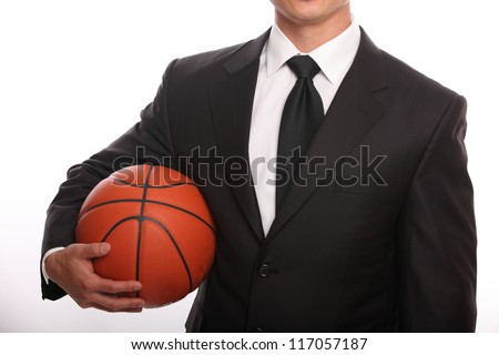 Businessman holding a basketball without a head - stock photo