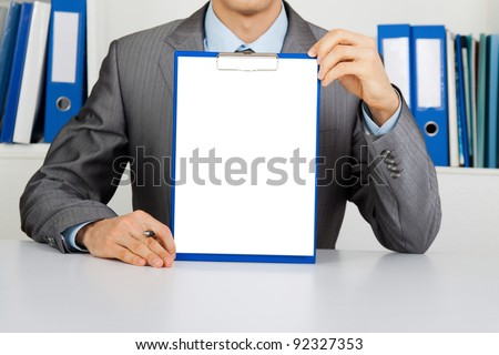 businessman holding a blank white board, signboard, clipboard with paper, showing an empty bill board with copy space for text, unrecognizable person sitting at the desk at office - stock photo