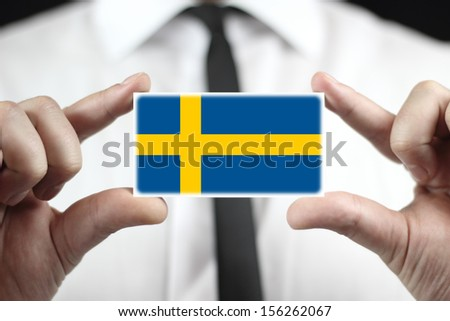 Businessman holding a business card with a Sweden Flag - stock photo