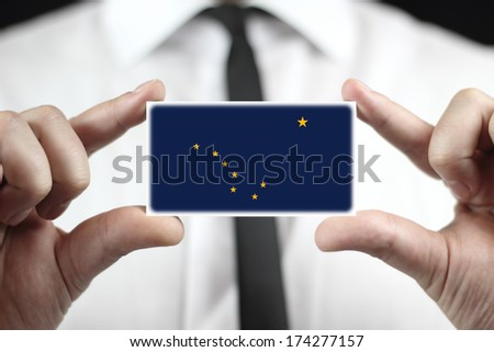 Businessman holding a business card with Alaska State Flag - stock photo